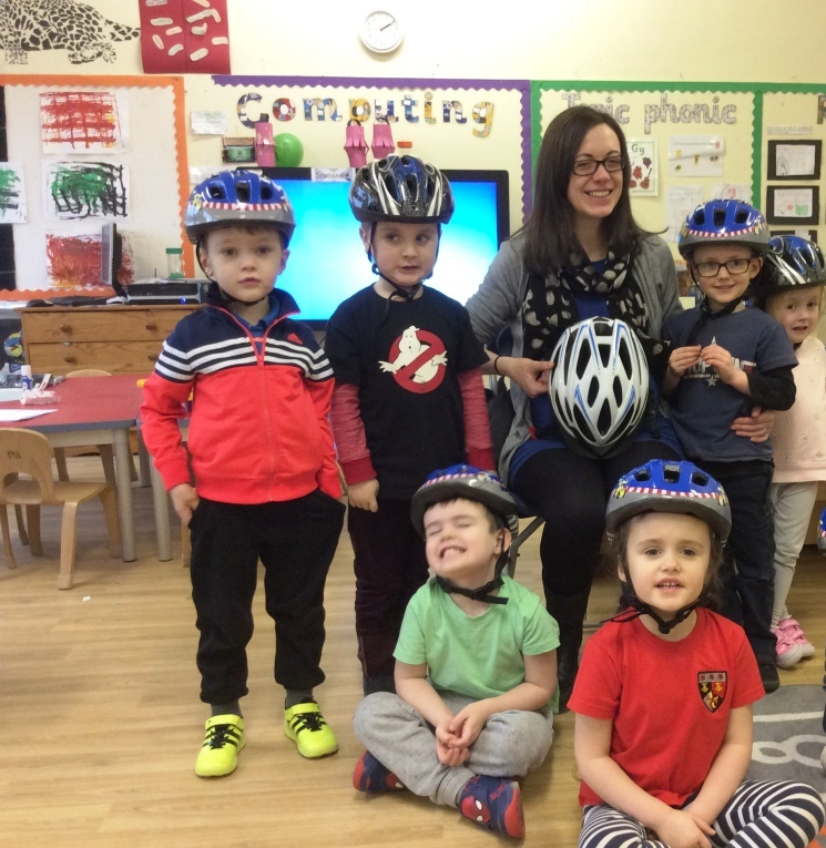 children with teacher wearing cycle helmets